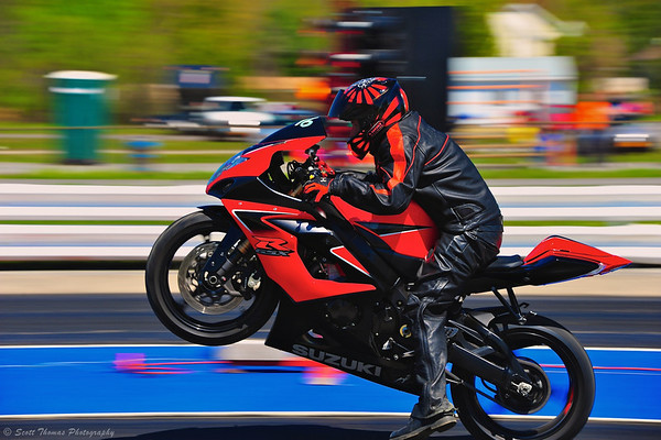 Panned photo of a motorcycle popping a wheelie at ESTA Safety Park Dragstrip.