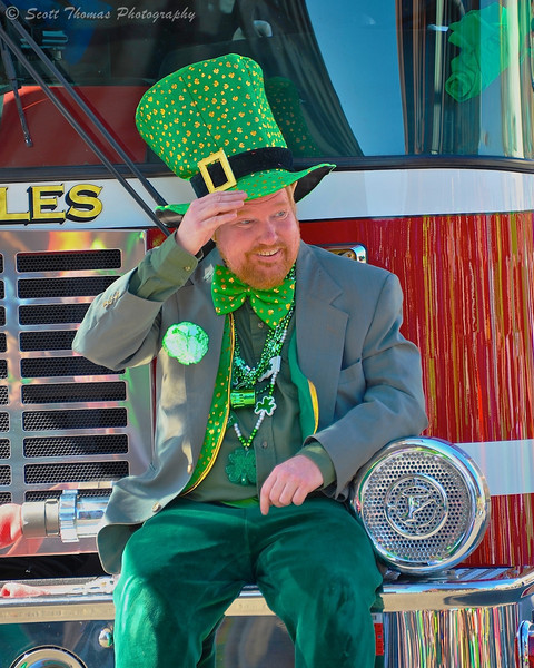 A leprechaun riding on the front bumper of a fire truck in the Syracuse St. Patrick's Day Parade in Syracuse, New York.
