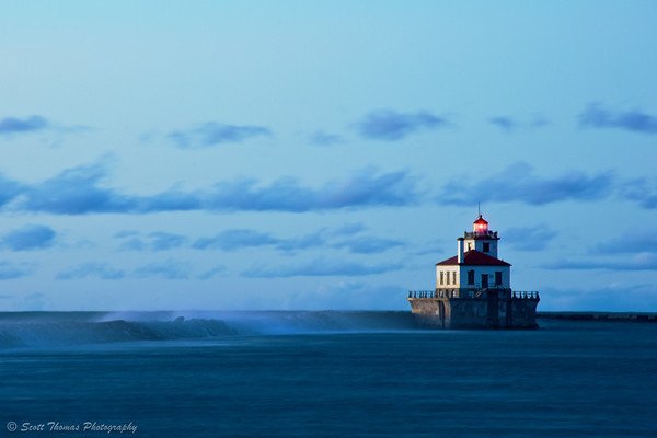 Waves whisper over the Oswego (New York) Harbor breakwall during a long exposure at dusk.