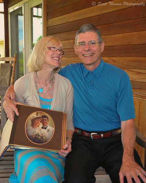 A couple celebrating their 25th Wedding Anniversary holding their wedding portrait.