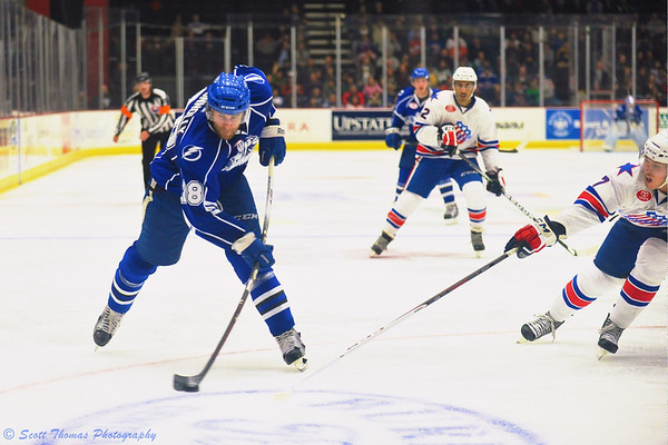 Syracuse Crunch Brett Connolly (28) leans into a shot against the Rochester Americans in the Onondaga County War Memorial.
