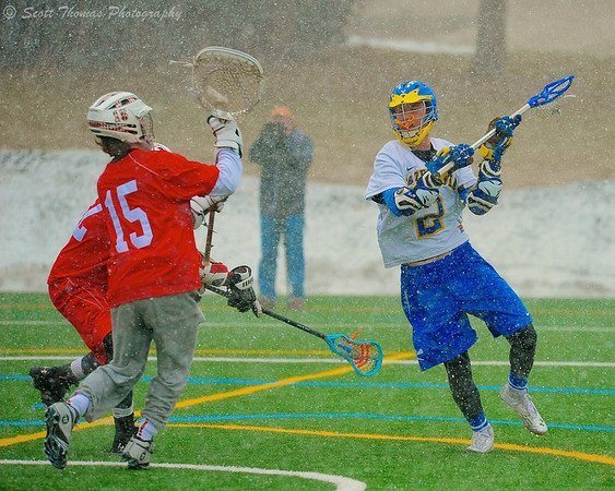 Cazenovia Lakers Henry Mann (2) lining up a shot at Baldwinsville Bees goalie Daniel Thomas (15) during a Spring snow shower on Saturday, April 5, 2015 at Cazenovia, New York.