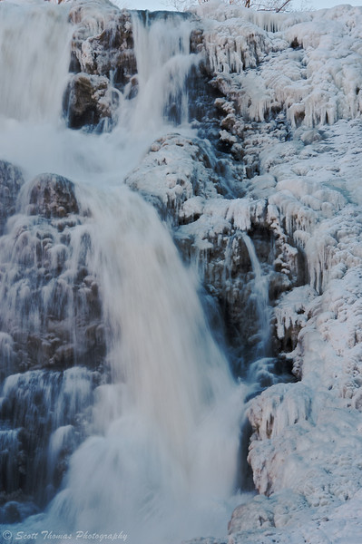 Water flows between the ice on Ithaca Falls near Ithaca, New York.