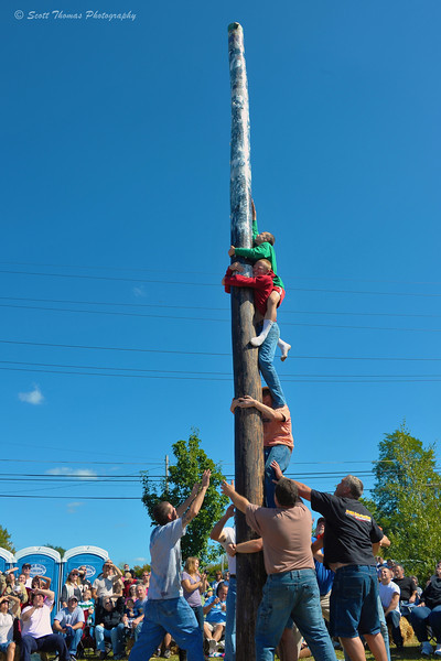 A team competes in the Adult Grease Pole Climb at the Jordan Fall Festival in Jordan, New York.