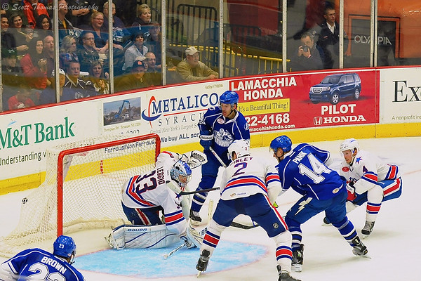 Syracuse Crunch Richard Panik (14) pots a goal against the Rochester Americans goaltender David Leggio (33).