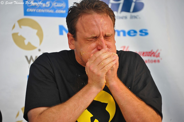 Joey Chestnut stuffing salt potatoes into his mouth during the Wild Carp Week World Salt Potato Eating Championship on Paper Mill Island Budweiser Amphitheater stage in Baldwinsville, New York.