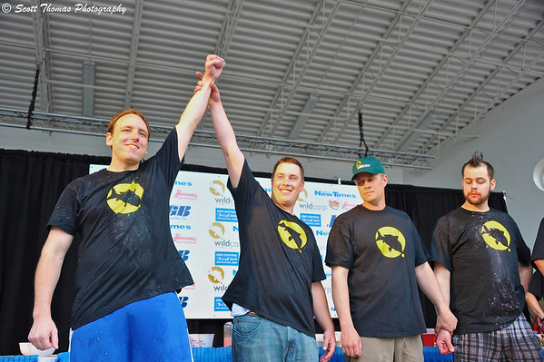 Promoter Jason Bernhardt: raises Wild Carp Week World Salt Potato Eating Champion and World Record Salt Potato Eating holder Joey Chestnut's arm in victory on Paper Mill Island Budweiser Amphitheater stage in Baldwinsville, New York. Joey ate 13 pounds of salt potatoes in 10 minutes to set a new world's record.