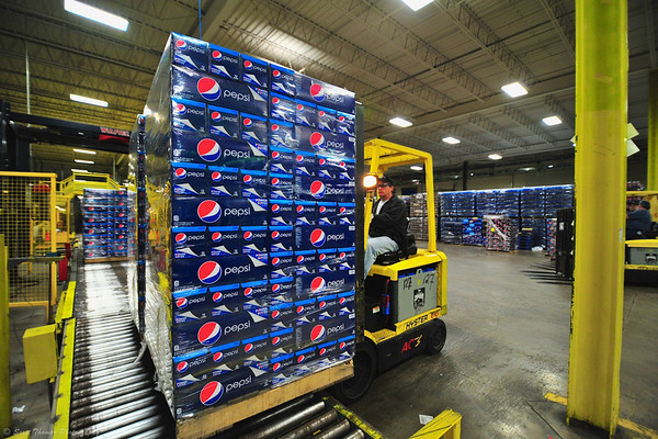 Pallets of Pepsi Cola Fridgemate packages are lifted off the production line.