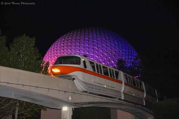 Monorail Orange passing Spaceship Earth at night.