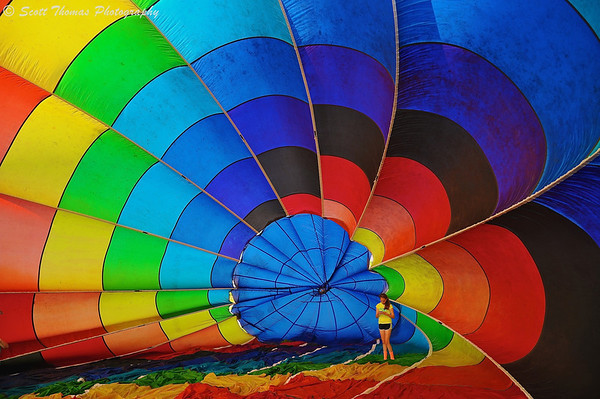 A young woman inside a rainbow colored hot air balloon at the Oswego Balloonfest at the Oswego Country Fairgrounds in Sandy Creek, New York. on Saturday, June 7, 2014.