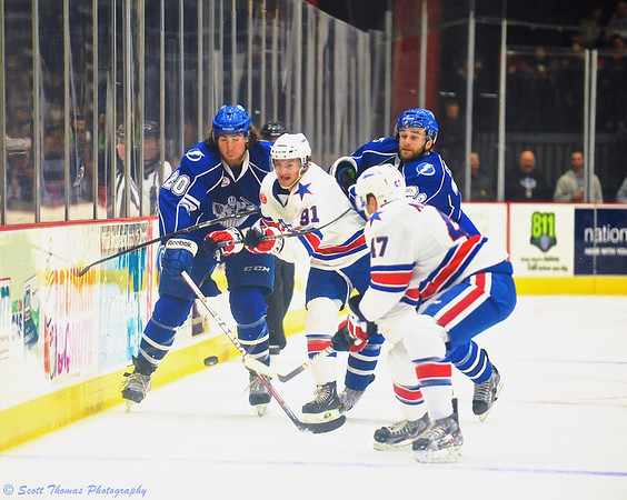 Syracuse Crunch players Pierre-Cedric Labrie (20) and Brett Connolly (28) fight for the puck along the boards agains Rochester Americans Frederick Roy (91) and Matt MacKenzie (47) in the Onondaga County War Memorial.