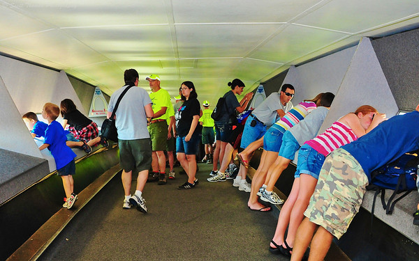 Tourists leaning close to the small windows at the top of the Gateway Arch in St. Louis, Missouri.