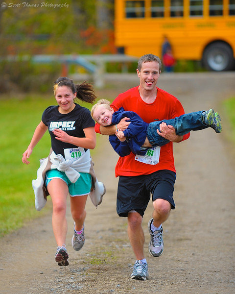 Mom and Dad pick up their son as they head to the finish line at the Apple Run 15K Road Race in LaFayette, New York.