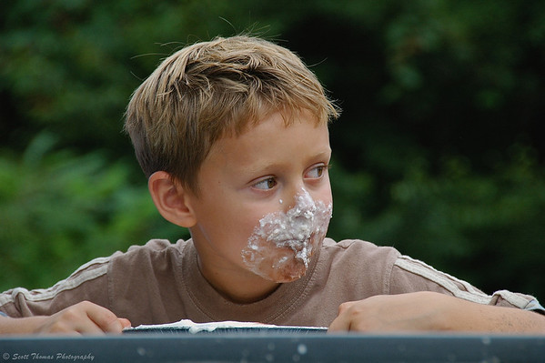 A boy looks up from his pie eating to check on his competitors at the Golden Harvest Festival in Baldwinsville, New York.