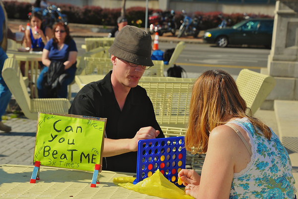Can You Beat Me? Guy in hat has fun at the 4th Annual Crawfish Festival with a Connect Four challenge at Clinton Square in Syracuse, New York.