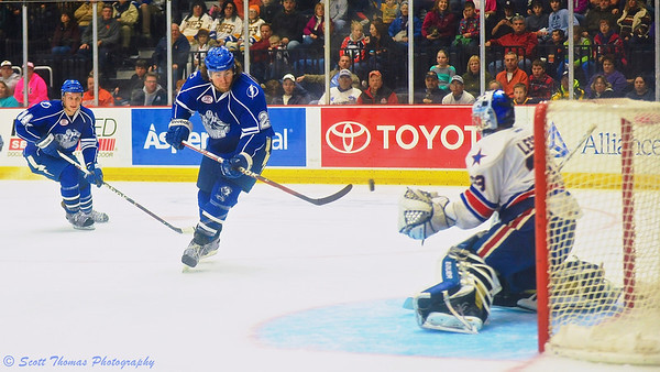 Syracuse Crunch Pierre-Cedric Labrie (20) backhands a shot at Rochester Americans netminder David Leggio (33).