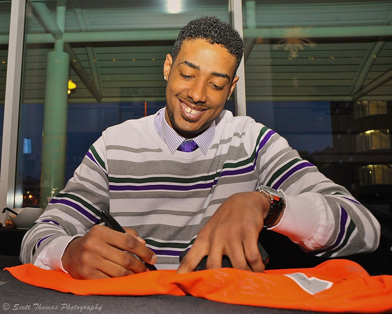 7 foot tall Sophomore center Fab Melo signing a fan's jersey at the 41st Annual Syracuse University Basketball Hardwood Club Dinner at the OnCenter in Syracuse, New York on Sunday, March 4, 2012.