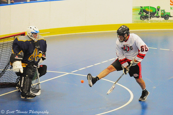 "Onondaga Red Hawks Brett Bucktooth (66) goes between the legs to score a goal against the Allegany Arrows in Can-Am Senior ""B"" Box Lacrosse league action at the Onondaga Nation Arena in Nedrow, New York."