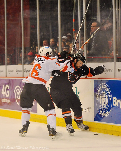 Syracuse Crunch Nicolas Deschamps (16) checks an Adirondack Phantoms player.