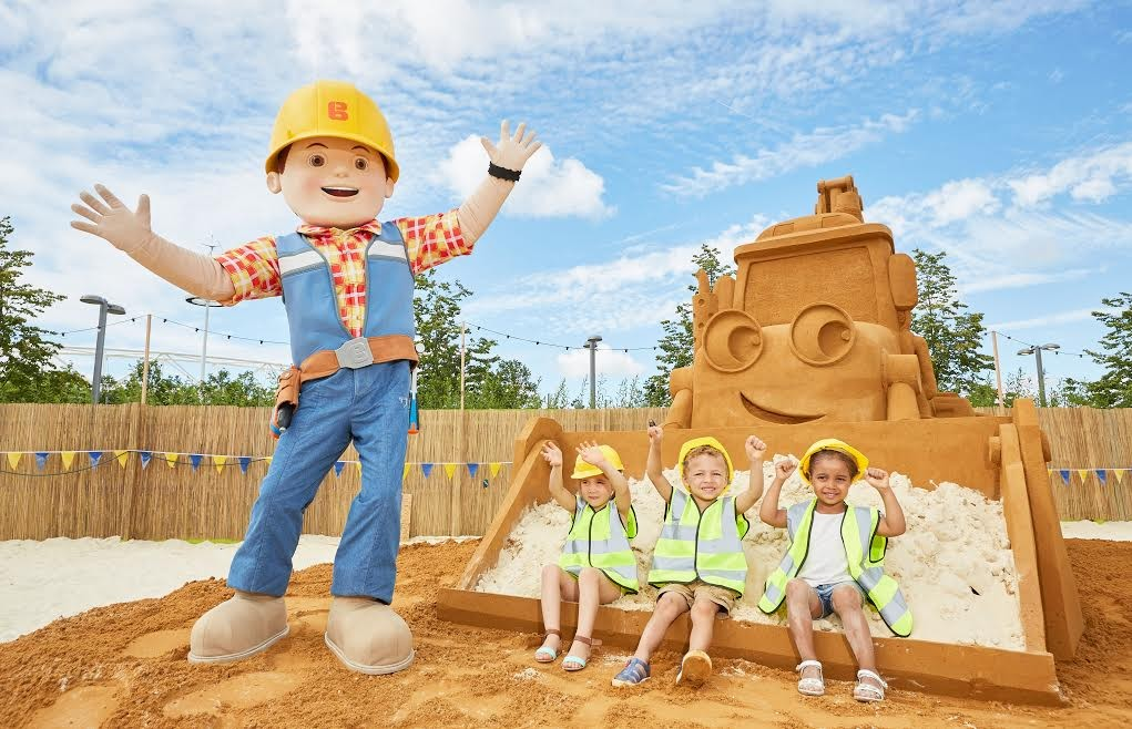 Kacey Francois aged 3, Sophia Drozd aged 4 and Kamari Bales Stennett aged 4 build sandcastles with Bob the Builder next to a 60 tonne sand sculpture