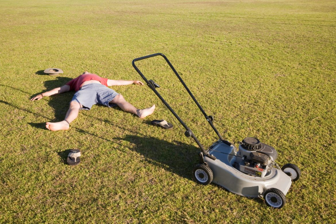 Man tired and lying on lawn after mowing garden. Gardening is great exercise.