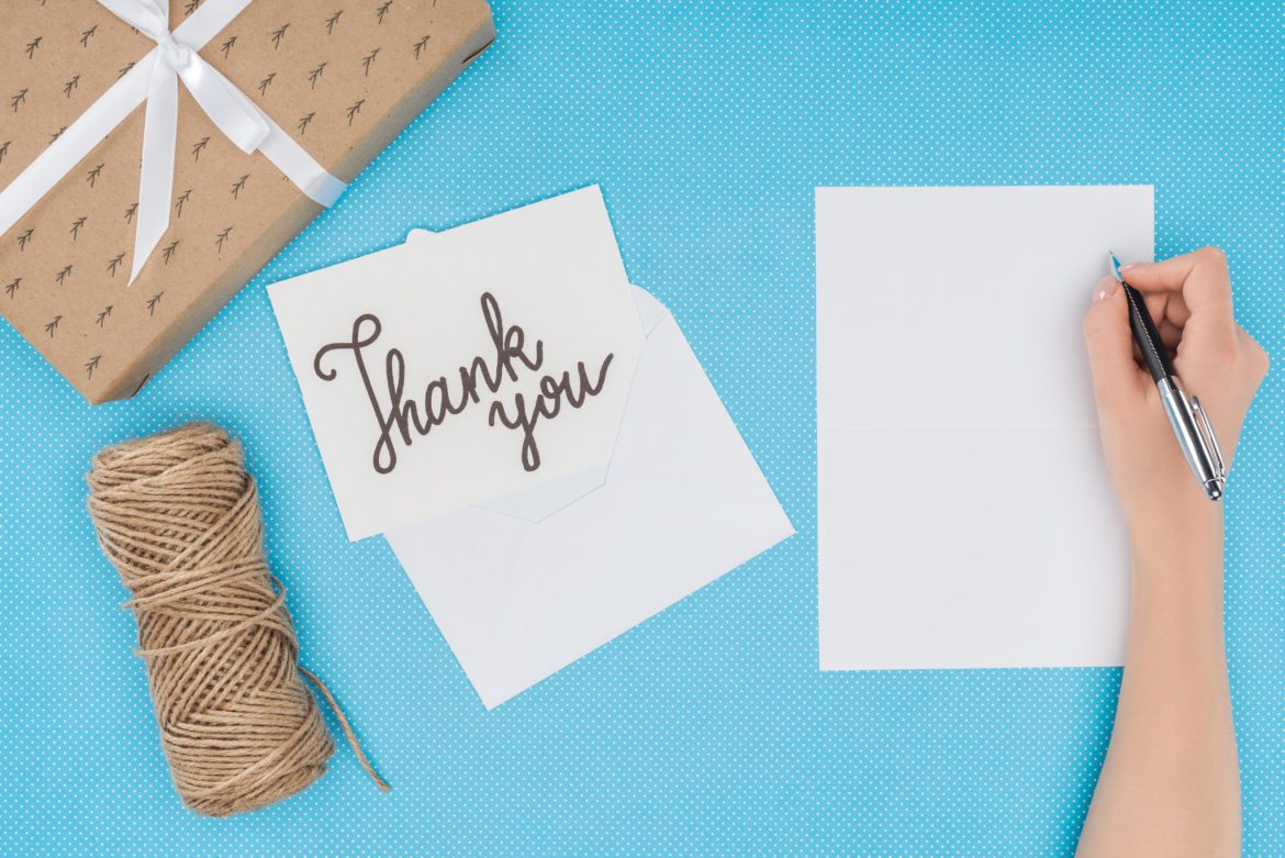 Somebody writing a thank you card on a desk top with a parcel and twine.