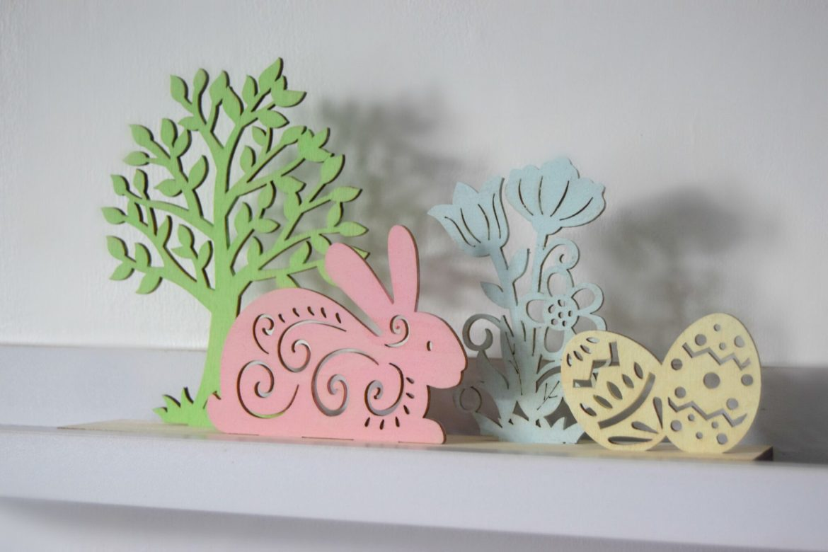 Wooden Easter scene with a tree, rabbit, flowers and eggs. Painted in pastel shades. Easter craft.