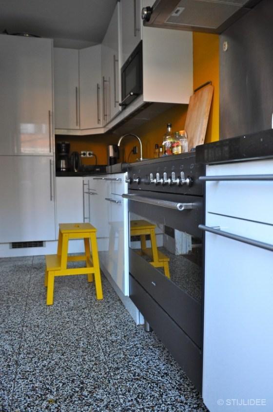 Moderne witte keuken met gele muur na STIJLIDEE Interieuradvies en Styling