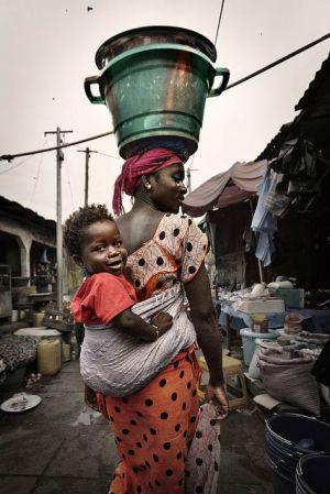 Afrikanische Mutter mit Baby auf dem Rücken und Last auf dem Kopf