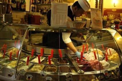 Worker scooping gelato in shop
