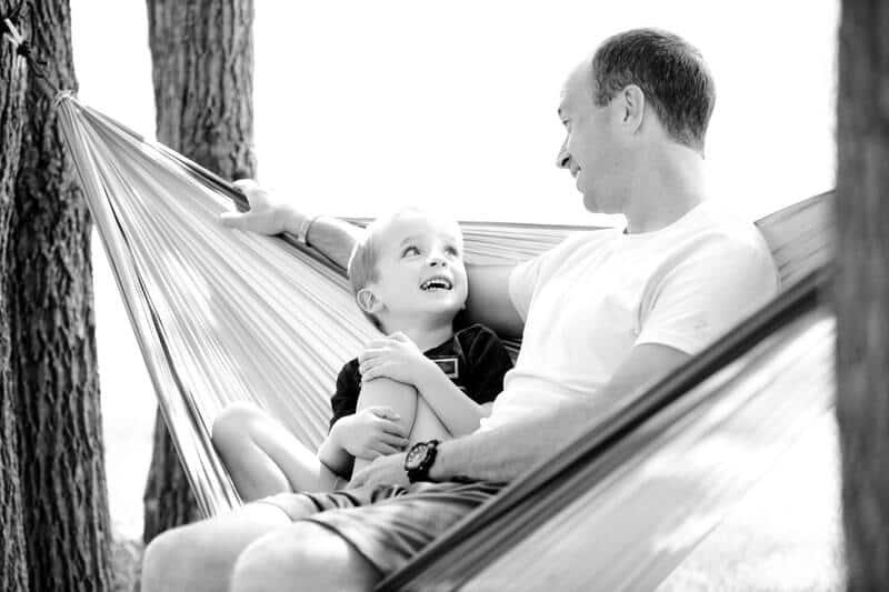 Black and white father and son bonding on hammock