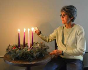 Sister Lyn Szymkiewicz lighting a candle for the fourth week of Advent.