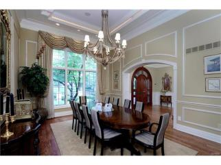 Arched doorway 12'ceiling with 7 piece crown molding and panel molding, exquisite chandelier, dramatic cove ceiling with accent lighting