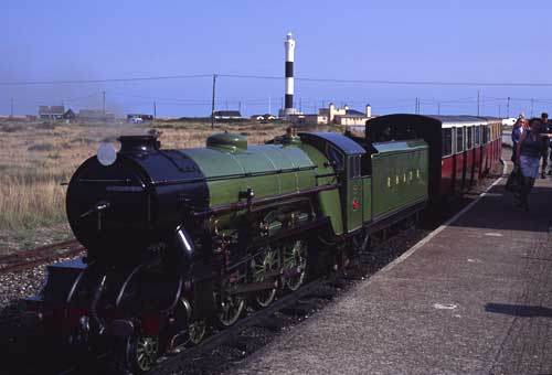 """""""Green Goddess"""" waits to work the 13.00 service to Hythe, with the new lighthouse in the background. The older lighthouse, out of shot to the right, is open to the public."""