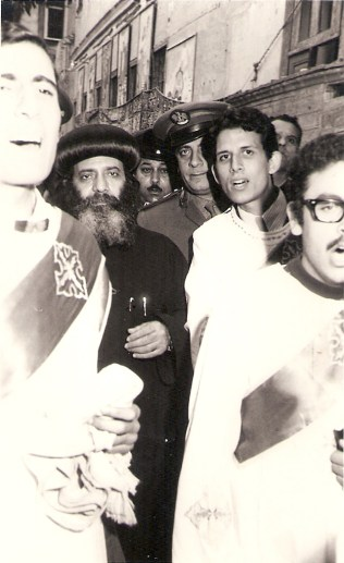 Welcoming Pope Shenouda III during his visit to attend the 100 years anniversary of Virgin Mary Church in Elsagha, Tanta, Egypt - 1975. In the picture, Father Metias (a deacon in that time) on the left of His Holiness Pope Shenouda III.