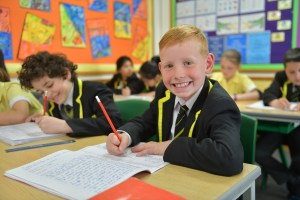 Boy smiling at his desk whilst working