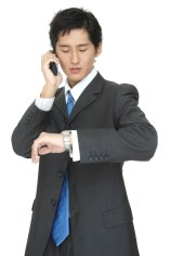 An asian businessman checks the time whist taking on the telephone