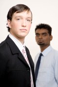 A smart caucasian businessman in a suit (in focus) with another businessman behind (out of focus)