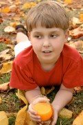 Autumn leaf fall and a boy with orange juice Focus on Foreground only