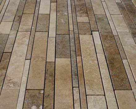 Die Oberfläche des Steins ist geschliffen und die Poren sind mit farbigem Zement verschlossen. Der Stein ist frostfest und auch für den Außenbereich verwendet.