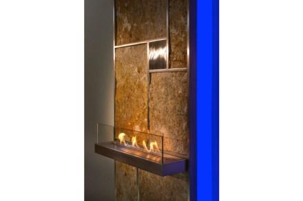 """""""Juwall"""": Pared con calefacción eléctrica detrás, en la que la piedra actúa como acumulador de calor. Con una mini-hoguera o soporte para toallas."""