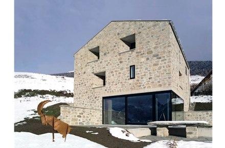 Beim dem Wohnhaus in Sent in der Schweiz wurde, wie früher üblich, für die Fassade Naturstein aus dem Aushub und aus einem nahen Bruch verwendet und mit Kalkstein vermörtelt.