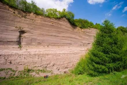Die Wingertsbergwand bei Mendig, im Vordergrund Besucher, lässt ahnen, welche Menge an Material beim Ausbruch des Laacher See-Vulkans ausgeworfen wurde. Foto: Kappest, Vulkanpark GmbH / Wikimedia Commons