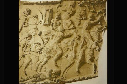 Jinetes enemigos con armadura huyen de la caballería romana.