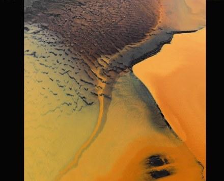 Farbe Orange: Eisenminerale aus dem Vulkanboden färben das Moorwasser, das an der Südküste Islands ins Meer geschwemmt wird. Foto: Bernhard Edmaier