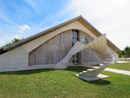 """Das Bild zeigt neben dem """"Segel"""" zwei weitere spektakuläre Steinbauten von Fallacara: das dreieckige Dach der Halle im Hintergrund ruht auf Bögen aus Bausteinen mit einem Stahlkabel im Inneren; rechts vorne eine selbsttragende Treppe."""