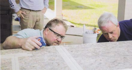 """Photo from """"Today's Homeowner with Danny Lipford"""" TV show about outdoor kitchen installation: host Danny Lipford (right) and an expert from Stone Interiors company. Photo taken from """"The Cutting Edge"""" magazine (May/June 2017) by MIA+BSI."""