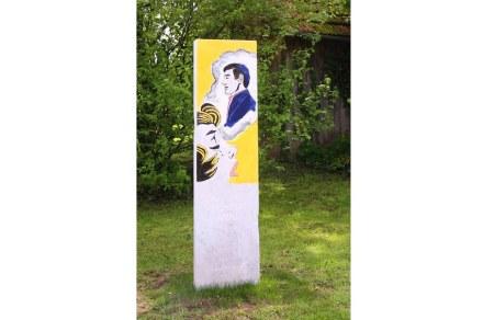 """Wolfgang Gollner: """"Bunte Antike"""". In der Antike waren Statuen meist bunt bemalt. Hier ist in den Marmor der Stele als Relief ein Bild von Roy Lichtenstein eingearbeitet, das eine trauernde junge Frau zeigt. Rundherum ist der Marmor mit der Farbe des Pop-Art-Bildes bemalt."""