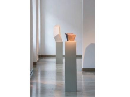 """Blick in die Ausstellung. Im Vordergrund die Skulptur """"Ohne Titel (Christoph Voll zum Gedenken)"""", roter schwedischer Granit aus dem Jahr 2002, im Hintergrund Ohne Titel, 1988-90, Marmor."""