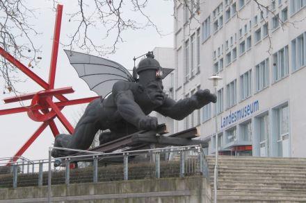 Fortschritt, so glaubte man in Zeitalter der Dampfmaschine, würde erreicht durch Geschwindigkeit, Technik und Eisen. Skulptur vor dem Eingang des Technoseums in Mannheim.